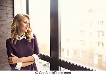 Attractive young woman near window at home
