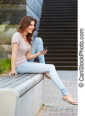 Attractive young woman on bench with mobile phone