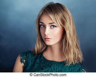Attractive young woman on blue background, closeup portrait