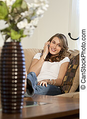Attractive Young Woman On Her Cell Phone At Home