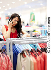 Attractive young woman on the phone at shopping