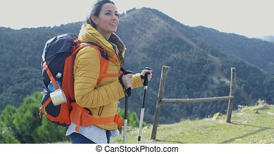 Attractive young woman out backpacking and hiking in the...