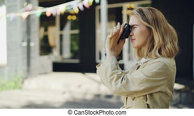 Attractive young woman photographer is taking pictures with...