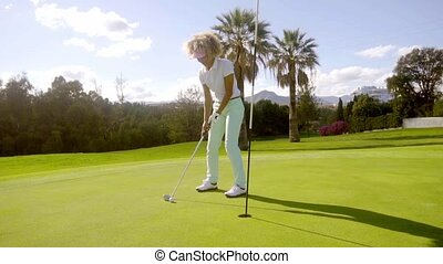 Attractive young woman playing a golf shot on the green of a...