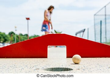 Attractive young woman playing mini golf. Shallow depth of field.