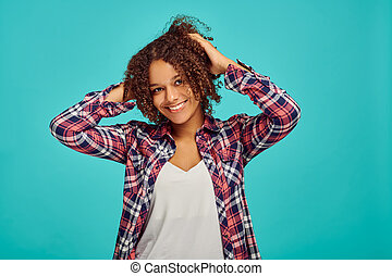 Attractive young woman portrait, blue background, positive emotion. Face expression, female person looking on camera in studio, emotional concept, feelings