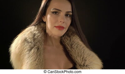 Attractive young woman posing in elegant fur jacket and sexy evening black dress