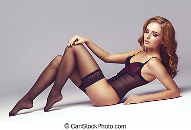 Attractive young woman posing in erotic lingerie. Sexy...