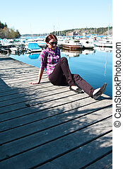 Attractive young woman posing near the harbor