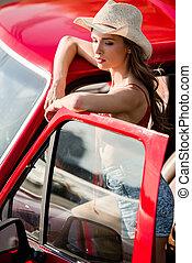 woman posing next to car