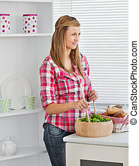 Attractive young woman preparing a salad