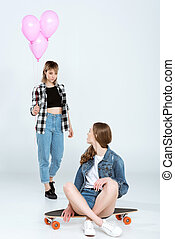 Attractive young woman presenting balloons to pretty girlfriend sitting on skateboard