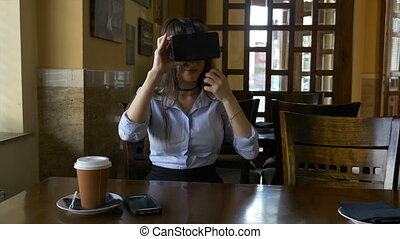 Attractive young woman puts on VR virtual reality glasses in coffee shop