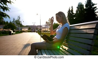 Attractive young woman reading a book sitting on the bench...