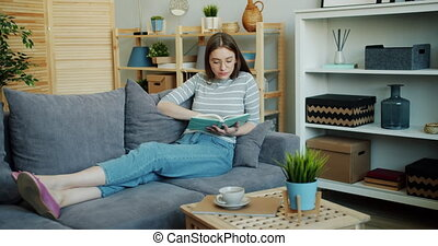 Attractive young woman reading interesting book enjoying...