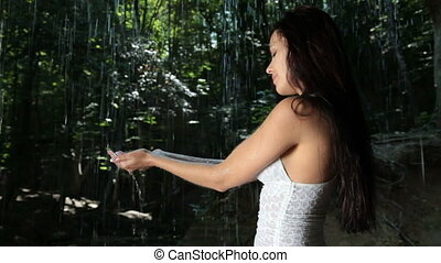 Attractive young woman refreshing under water jets of mountain waterfall in the summer woods