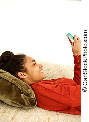 Attractive young woman relaxing at home using cellphone