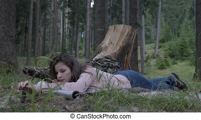 Attractive young woman resting down the grass in the woods enjoying silence and nature taking a break from hike