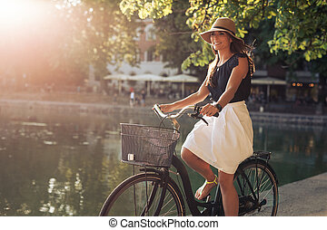 Attractive young woman riding bicycle along a pond in city park