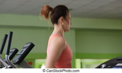 Attractive young woman running on a treadmill