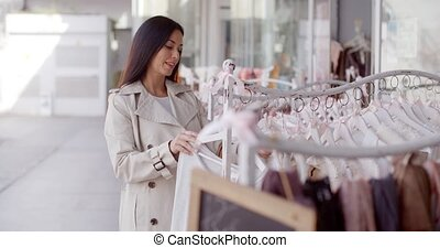 Attractive young woman shopping for clothing going through garments on a rack in a boutique searching for something suitable
