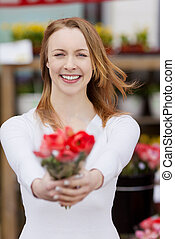 Attractive young woman showing a bunch of flowers