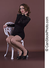 Attractive young woman sits on a chair