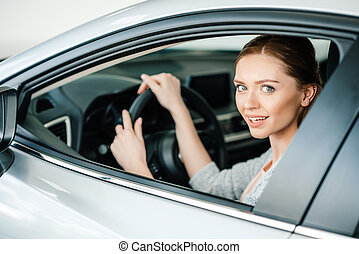 Attractive young woman sitting in new car and smiling at camera