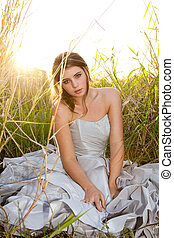 An attractive young woman wearing formal attire is sitting in a grass field. Vertical shot.