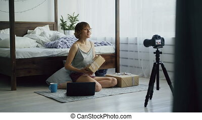 Attractive young woman sitting near bed recording video blog about packing gift box with dslr camera