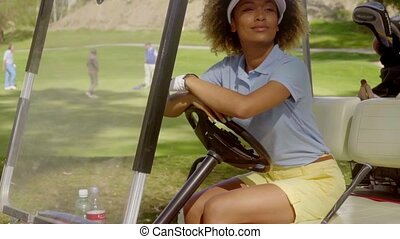 Attractive young woman sitting on a golf cart