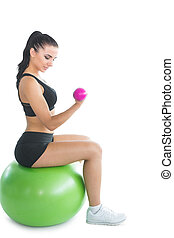 Attractive young woman sitting on an exercise ball using pink dumbbells on white screen