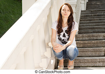 Attractive young woman sitting on steps