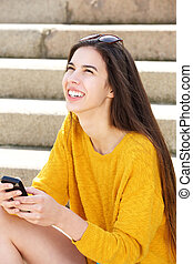 Attractive young woman sitting on steps holding cellphone