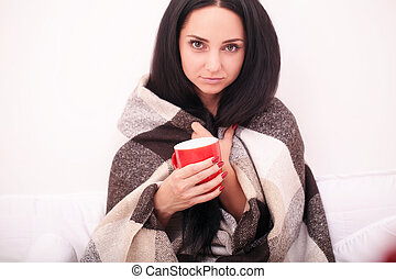 Attractive young woman sitting with a cup of coffee in a white bed