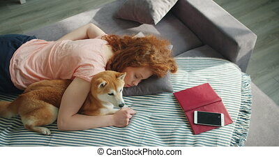 Attractive young woman sleeping at home on sofa hugging cute...