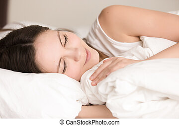 Attractive young woman sleeping comfortably in bed, close up hea