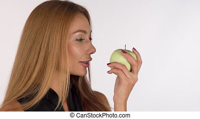 Attractive young woman smelling delicious green apple, smiling cheerfully