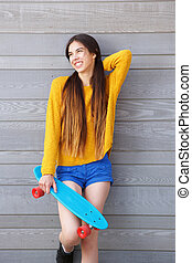 Attractive young woman smiling against wall with skateboard