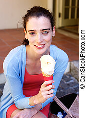 Attractive young woman smiling and eating ice cream outside