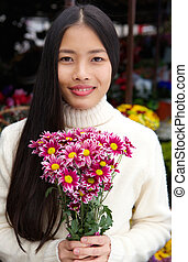 Attractive young woman smiling and holding flowers