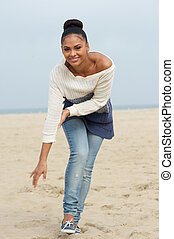 Attractive young woman smiling and walking on beach