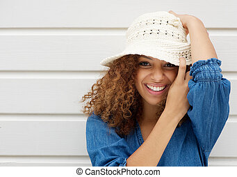 Attractive young woman smiling and wearing hat on white background
