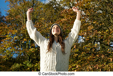 Attractive young woman smiling outdoors with arms outstretched