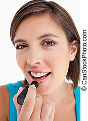 Attractive young woman smiling while applying lipstick against a white background