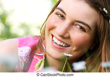 Attractive young woman smiling with flower outdoors