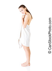 Attractive young woman standing in a towel.