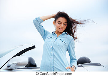 Attractive young woman standing near her new car