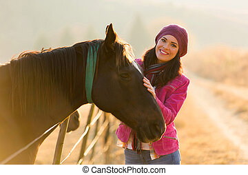 young woman standing next to a horse