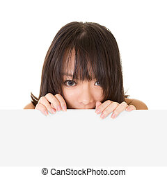 Attractive young woman looking at you behind blank wall,...